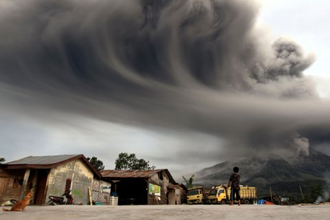 A woman in Sibintun village, Indonesia, watches as Mount Sinabung spews ash on Nov. 18, 2013.