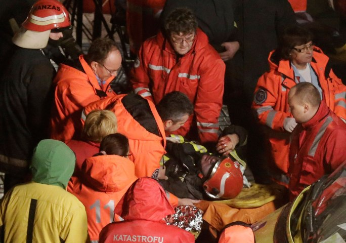 Paramedics inspect a firefighter on a stretcher after he was moved from the collapsed Maxima supermarket in Riga, on Nov. 21, 2013.