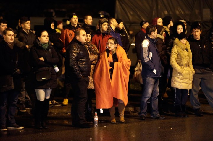 People gather near the collapsed Maxima supermarket in Riga, on Nov. 21, 2013.