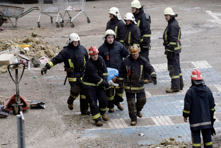 Firefighters carry a body as they remove it from a collapsed supermarket in Riga, on Nov. 22, 2013.