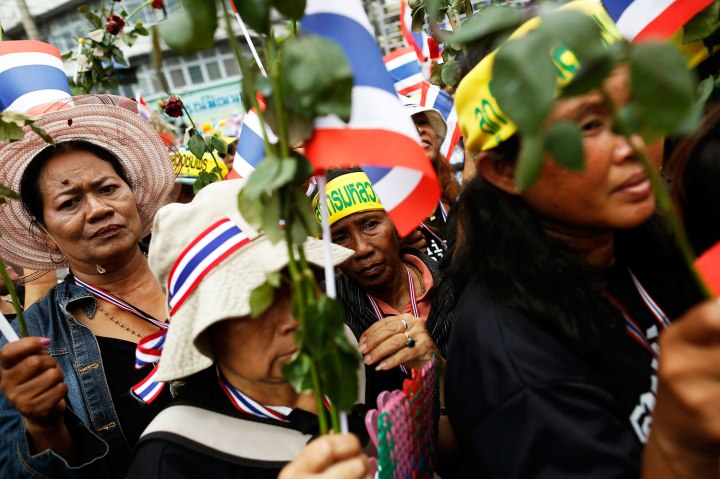 Anti-government protesters hold flowers before giving them to policemen at a barricade near a government building, chosen as a protest site, in Bangkok