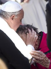 Pope Francis caresses a sick person in Saint Peter's Square at the end of his General Audience in Vatican City, Nov. 6, 2013.