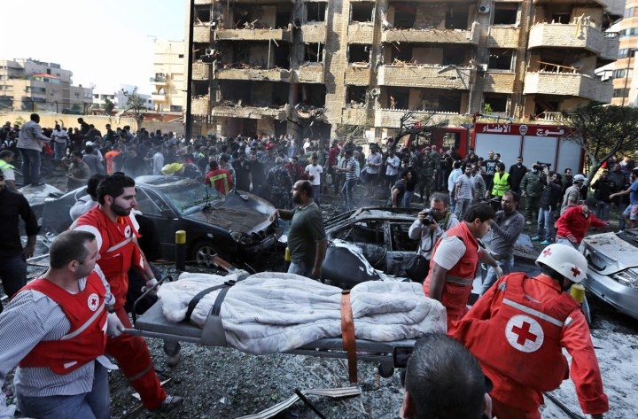 Lebanese Red Cross workers carry a dead body at the scene where two explosions have struck near the Iranian Embassy, in Beirut, on Nov. 19, 2013.