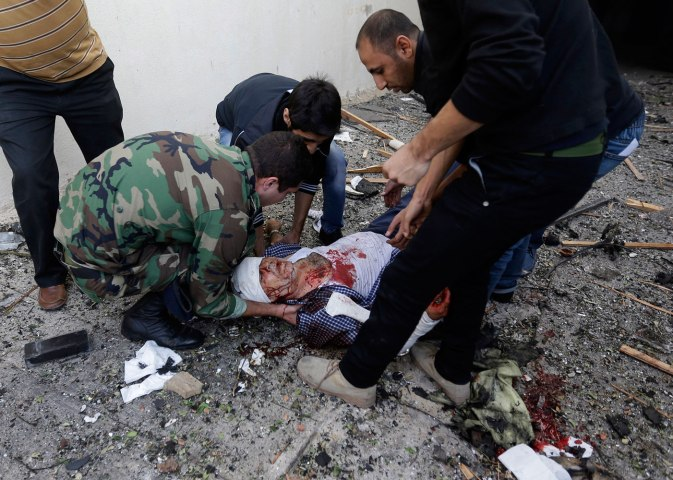 A Lebanese soldier and citizens help an injured man on the ground, at the scene where two explosions have struck near the Iranian Embassy, in Beirut, on Nov. 19, 2013.