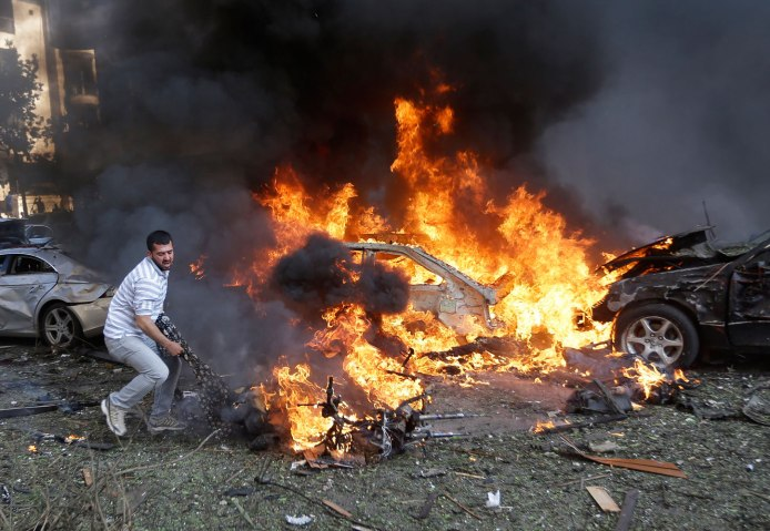 A Lebanese man tries to pull a dead body out of a burned car, at the scene where two explosions have struck near the Iranian Embassy killing several, in Beirut, on Nov. 19, 2013.