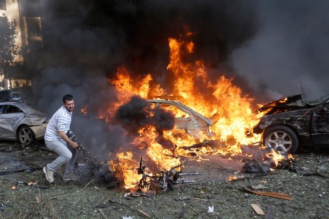 A Lebanese man tries to pull a dead body out of a burned car at the scene where two explosions have struck near the Iranian Embassy in Beirut, on Nov. 19, 2013.