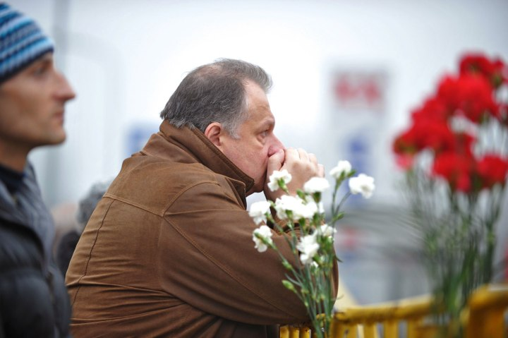 A man waits for news at the scene where the Maxima supermarket roof collapsed in Riga on Nov. 22, 2013.