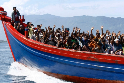 Ethnic Rohingya refugees from Myanmar wave as they are transported by a wooden boat to a temporary shelter in Krueng Raya in Aceh Besar