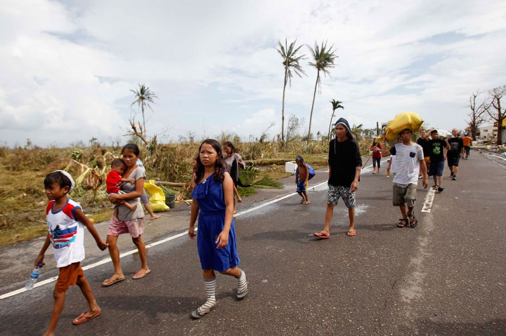 Survivors walk past a damaged town after strong winds brought by super Typhoon Haiyan battered Tacloban city
