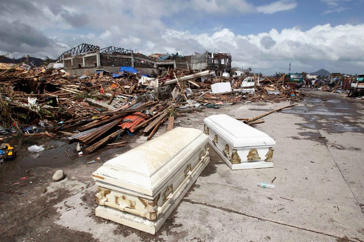 Empty coffins lie on a street near houses damaged after super Typhoon Haiyan battered Tacloban city