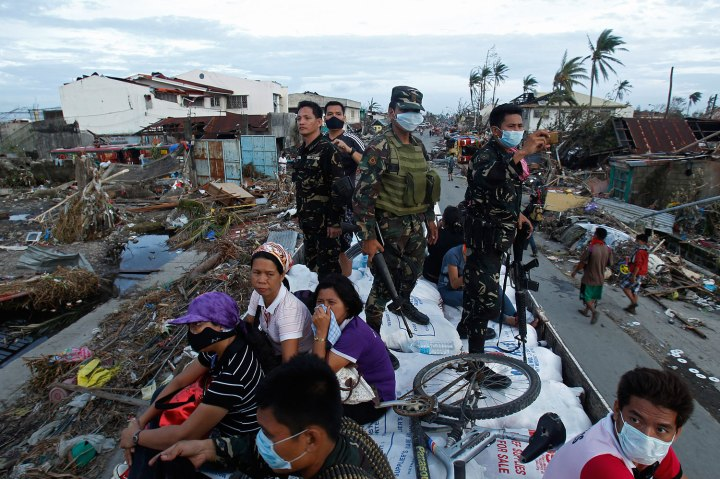 Soldiers and residents look at the devastation of the town from a military aid supplies distribution truck after the Super typhoon Haiyan battered Tacloban city