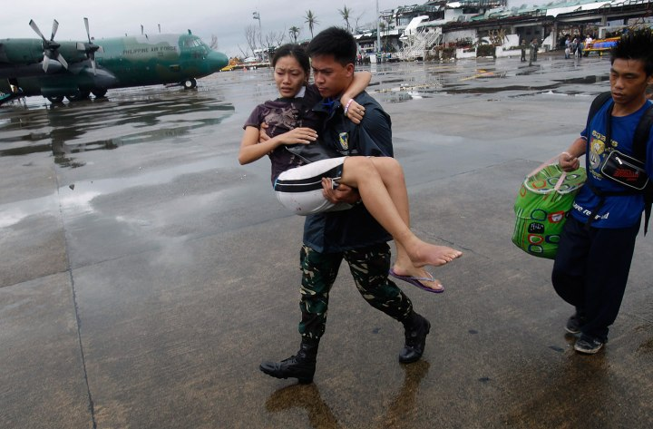 A military personnel carries a woman who had injured her leg, to a military C-130 aircraft leaving for Manila, after super typhoon Haiyan battered Tacloban City in central Philippines