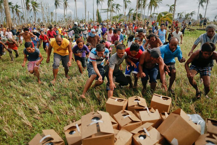 Survivors of Typhoon Haiyan rush to grab fresh water delivered by a U.S. military helicopter to their isolated village north of Tacloban