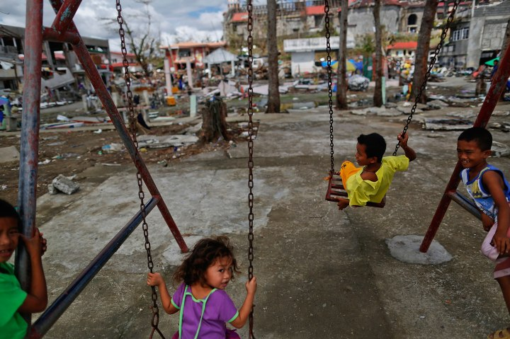 Children, survivors of Typhoon Haiyan, play on swings at a devastated area of Basey, north of Tacloban