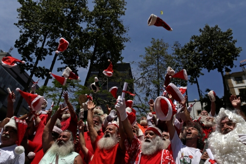 Students from the Brazilian Santa Claus school throw their hats into the air, during their graduation ceremony in Rio de Janeiro