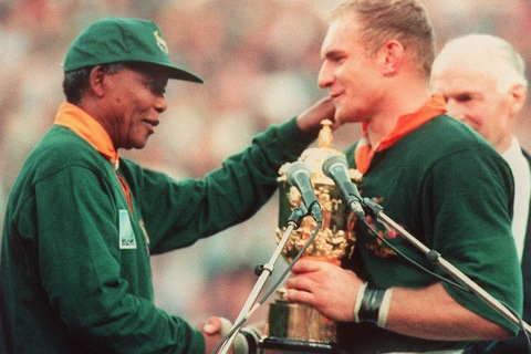 South Africa's president Nelson Mandela congratulates South Africa's rugby team captain François Pienaar before handing him the William Webb trophy after his team's victory over New Zealand in the final of the Rugby World Cup at Ellis Park in Johannesburg, June 24, 1995.