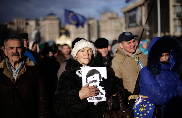 "A protester holds a portrait of Ukraine's President Viktor Yanukovich that reads ""Sign!"" during a demonstration in Kiev"