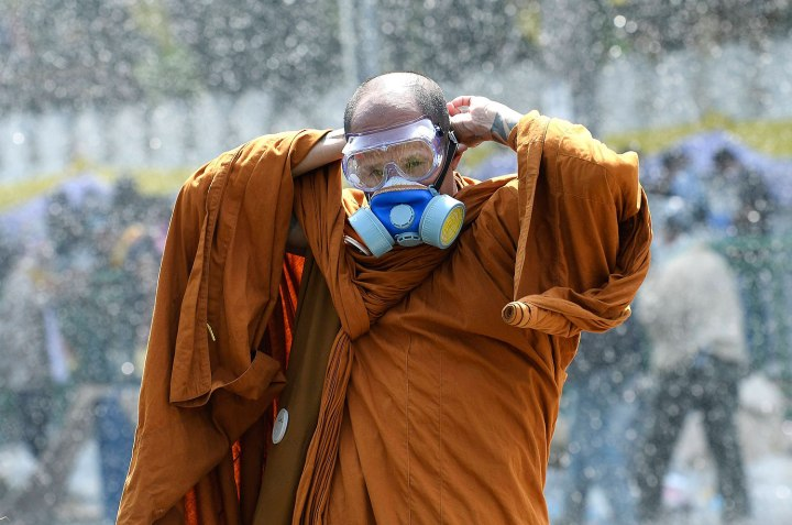 A Thai Buddhist monk puts on a gas mask as riot police use water cannon and tear gas while anti-government protesters attempt to remove barricades outside Government House in Bangkok