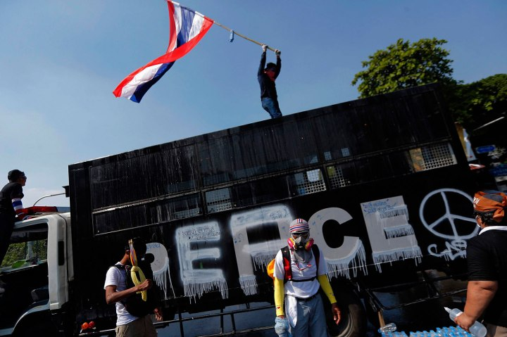 Anti-government protesters celebrate around a police truck as they get closer to the Government house during clashes in Bangkok