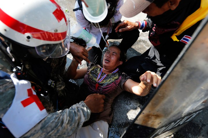 An injured anti-government protester is helped during clashes with police near the Government House in Bangkok