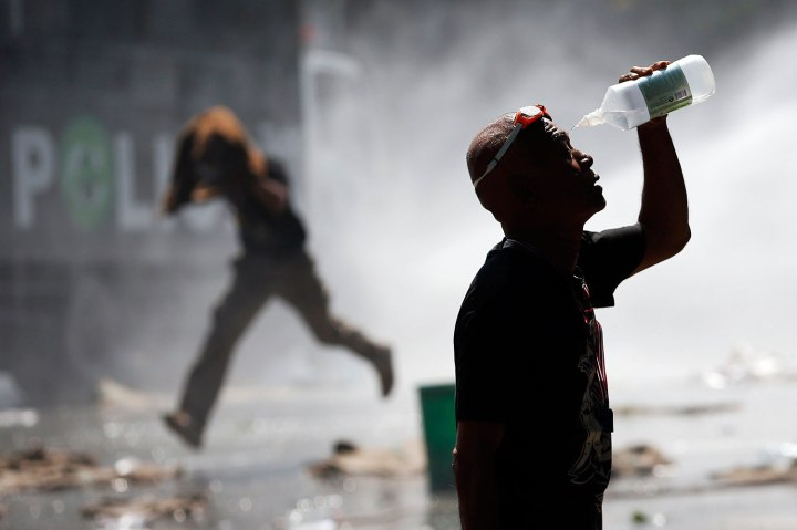 An anti-government protester recovers from teargas as another runs from water cannon during clashes with police at the barricade in front of the Government House in Bangkok