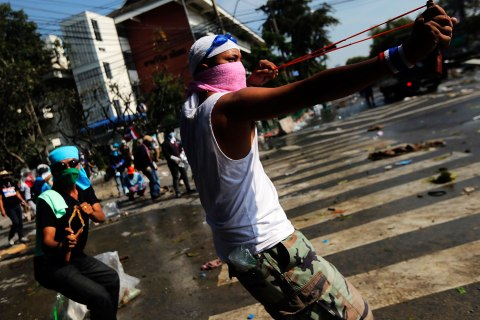 Anti-government protesters use slingshots during clashes with police at the barricade in front of the Government house in Bangkok