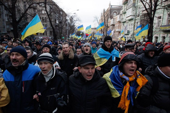 Protestors wave flags and shout slogans during a demonstration in support of EU integration in Kiev