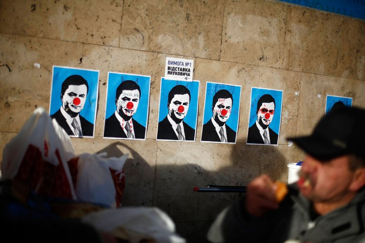 A man eats next to defaced posters depicting Ukranian President Viktor Yanukovich at Independence Square in Kiev