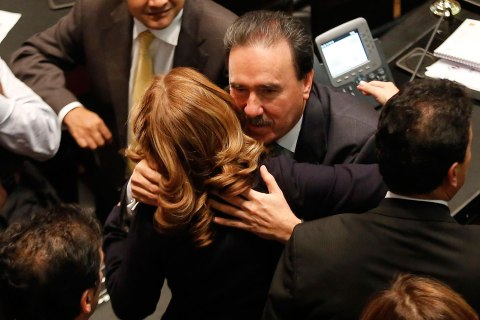 Senator Gamboa embraces a PRI senator after Mexico's Senate signed off on an energy bill at the Senate building in Mexico City