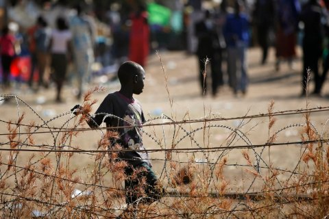 An internally displaced boy walks next to barbed wire inside a United Nations Missions in Sudan (UNMIS) compound in Juba, on Dec. 19, 2013.