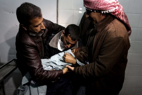 A Palestinian relative carries the lifeless body of Hala Abu Sebakha, who medics said was killed by shrapnel during an Israeli air strike on the Al Maghazi camp, at the morgue of Al-Aqsa hospital in Deir Al Balah, central Gaza Strip, on Dec. 24, 2013.