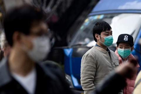 People wear masks while walking on a street during a hazy day in downtown Shanghai