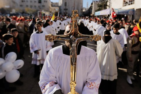 A priest holds a cross as he awaits the arrival of the Latin Patriarch of Jerusalem Fouad Twal, outside the Church of Nativity, the site revered as the birthplace of Jesus, during Christmas celebrations in the West Bank town of Bethlehem on Dec. 24, 2013.