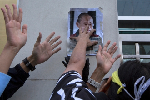 Pro-democracy activist Lui Yuk-lin posts picture of Liu Xia, wife of jailed Nobel Peace Prize Laureate Liu Xiaobo, on wall during protest calling for the freeing of Chinese dissidents outside Chinese liaison office in Hong Kong