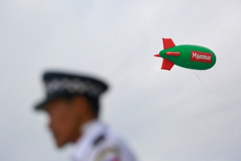 An advertisement balloon of the 27th SEA Games is pictured above a stadium as a police stands guard nearby in Naypyitaw