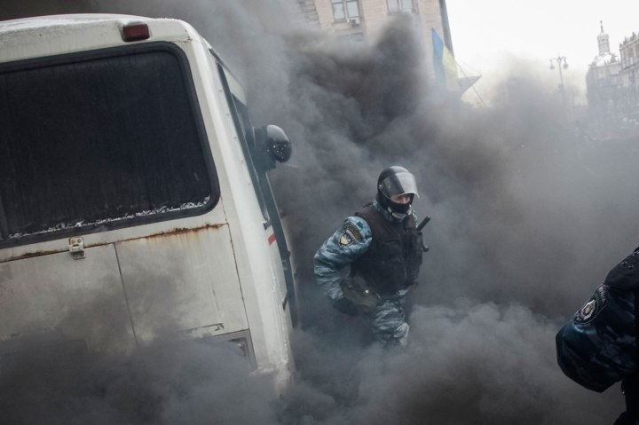A Ukrainian riot police leaves a bus after protesters threw a smoke grenade, outside City Hall in Kiev