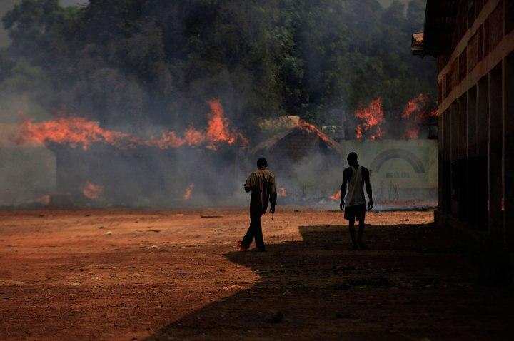Youths walk towards burning houses in Bossangoa