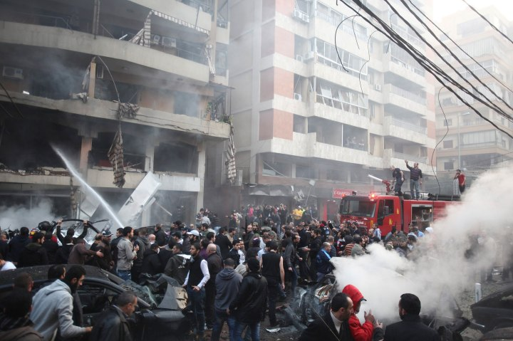 People gather as firefighters attempt to extinguish a fire at the site of an explosion in Beirut's southern suburbs