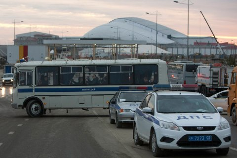 Russian police officers sit on a bus at an access road near venues at the Olympic Park near Sochi