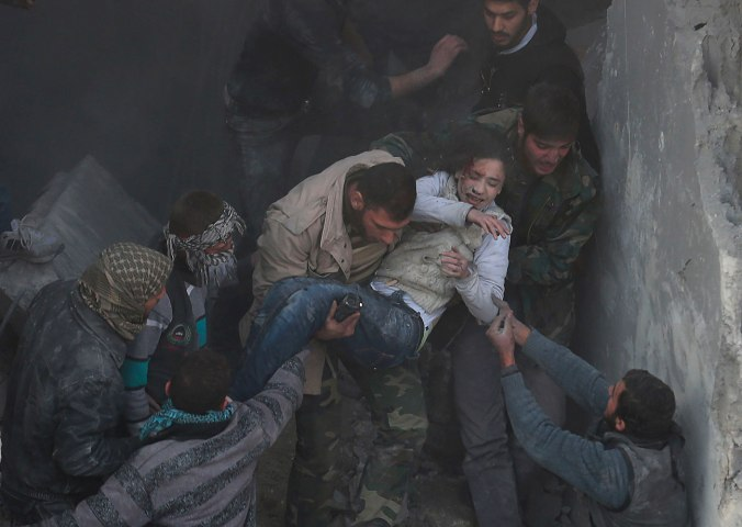 Men help a wounded girl who survived what activists say was an airstrike by forces loyal to Syrian President Bashar al-Assad in the Duma neighbourhood of Damascus
