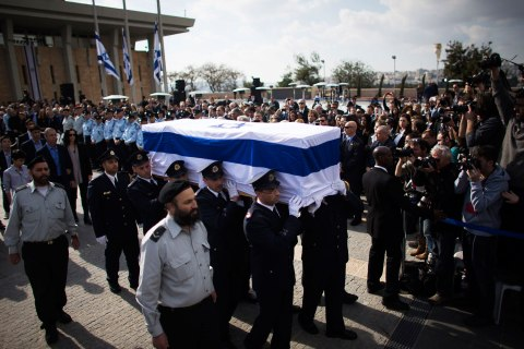 Members of the Knesset guard carry the flag draped coffin of former Israeli PM Sharon as his family members walk behind during a memorial ceremony at Israel's parliament in Jerusalem