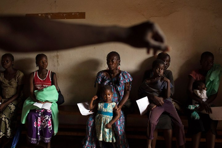 Mothers wait to have their children examined at a Medecins Sans Frontieres (MSF) clinic in a camp for internally displaced persons (IDPs) at the airport of the capital Bangui