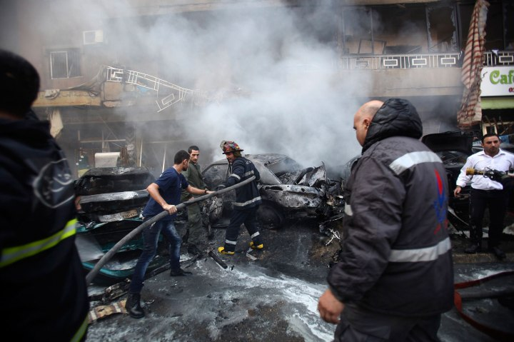 Firefighters extinguish a fire at the site of an explosion in the Haret Hreik area, in the southern suburbs of the Lebanese capital Beirut