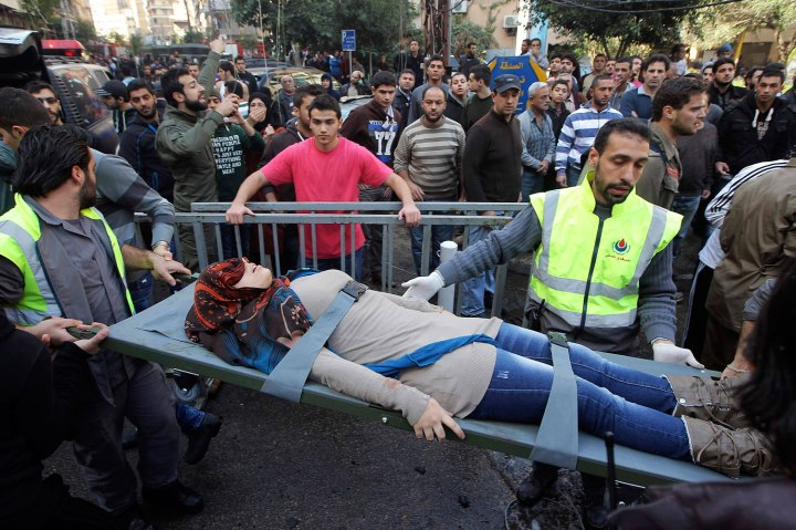 Civil defence personnel carry a wounded woman on a stretcher at the site of an explosion in the Haret Hreik area, in the southern suburbs of the Lebanese capital Beirut