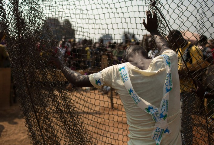 A man stands by a fence at the edge of a camp for internally displaced persons (IDPs) at the airport of the capital Bangui
