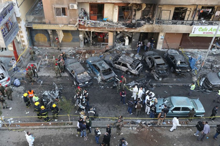 Lebanese army soldiers and forensic inspectors gather to examine the site of an explosion in the Haret Hreik area in the southern suburbs of  Beirut