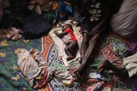 A baby sleeps next to a woman in a Catholic church in Malakal