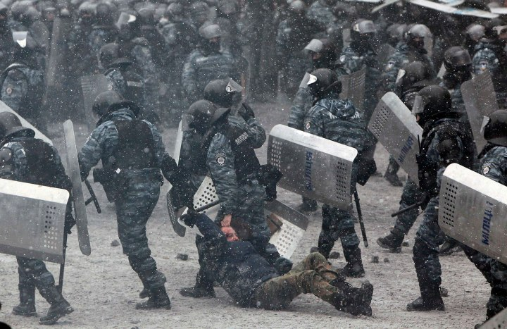 Riot police officers hold a man during clashes with pro-European protesters in Kiev