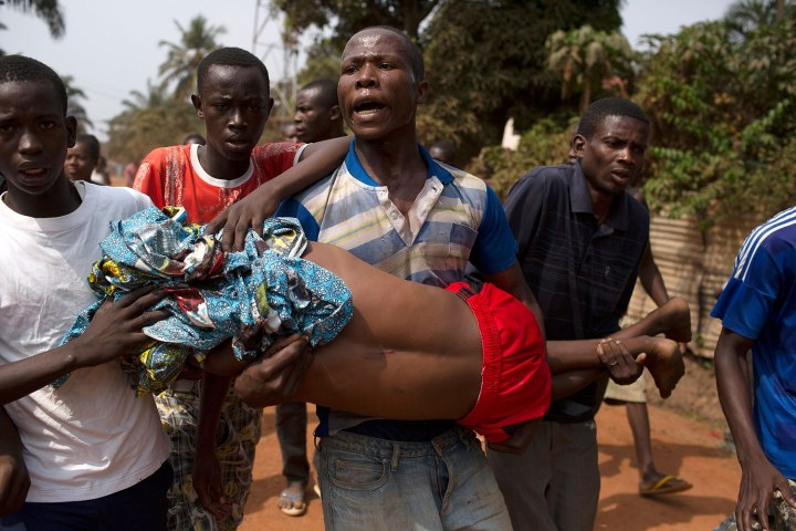 Men carry a boy, who died shortly after from a gunshot wound during a violent confrontation between Muslims and Christians, in Miskine district in Bangui