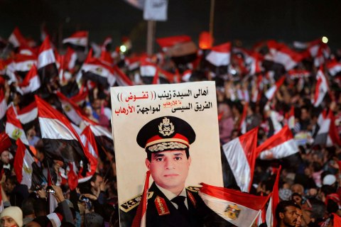 Supporters of Egypt's army chief General Abdul Fattah al-Sisi holds a poster of Sisi in Tahrir square in Cairo